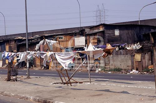 Sao Paulo, Brazil. Favela Vila Prudente shanty town; washing in front of rough wooden shacks.