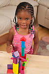 Four year old girl with consruction made from colored wooden blocks proud of her work vertical