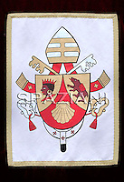 "The coat of arms of Pope Benedict XVI...The coat of arms of Pope Benedict XVI.The coat of arms of Pope Benedict XVI was designed by then Archbishop Andrea Cordero Lanza di Montezemolo (who later was created a Cardinal) soon after the papal election. Benedict's coat of arms has omitted the papal tiara, which traditionally appears in the background to designate the Pope's position as a worldly ruler like a king, replacing it with a simple mitre, emphasising his spiritual authority.[142] . .Escutcheon Gules, chape in or, with the....more ».The coat of arms of Pope Benedict XVI.The coat of arms of Pope Benedict XVI was designed by then Archbishop Andrea Cordero Lanza di Montezemolo (who later was created a Cardinal) soon after the papal election. Benedict's coat of arms has omitted the papal tiara, which traditionally appears in the background to designate the Pope's position as a worldly ruler like a king, replacing it with a simple mitre, emphasising his spiritual authority.[142] . .Escutcheon Gules, chape in or, with the scallop shell of the second; the dexter chape with a moor's head in natural colour, crowned and collared of the first, the sinister chape a bear trippant in natural colour, carrying a pack gules belted sable . .Symbolism Scallop shell: The symbolism of the scallop shell is multiple, one of the meanings is thought to represent Saint Augustine. While a doctoral candidate in 1953, Fr. Joseph Ratzinger wrote his dissertation on The People of God and the House of God in Augustine's Teaching is always about the Church, and therefore has a personal connection with the thought of this great Doctor of the Church..Moor of Freising: The Moor's head is an heraldic charge associated with Freising, Germany..Corbinian's bear: A legend states that while travelling to Rome, Saint Corbinian's pack horse was killed by a bear. He commanded the bear to carry the load. Once he arrived, he released it from his service, and it returned to Bavaria. The implication is that ""C"
