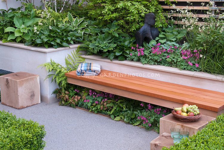 Foliage Garden & patio, raised beds, with wooden bench, blanket, Dicentra bleeding hearts above bench