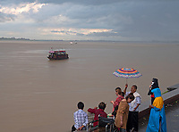 People gathering for a small ceremony even during the rain. A rainstorm over the Mekong River in Phnom Penh, Cambodia Monsoon Season in Phnom Penh