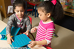 Education preschool 3-4 year olds two girls working together building with pegs and peg boards