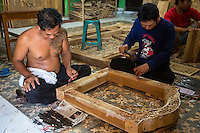 Bali, Indonesia.  Woodcarvers Working on Window Frames in Workshop.