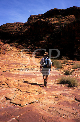 Kings Canyon, Australia. Tour guide treks across red rocky terrain at top of Kings Canyon.