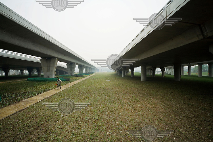 A peasant returns from tending to the newly planted grass just below the new highway and metro line that lead to Beijing's new airport.