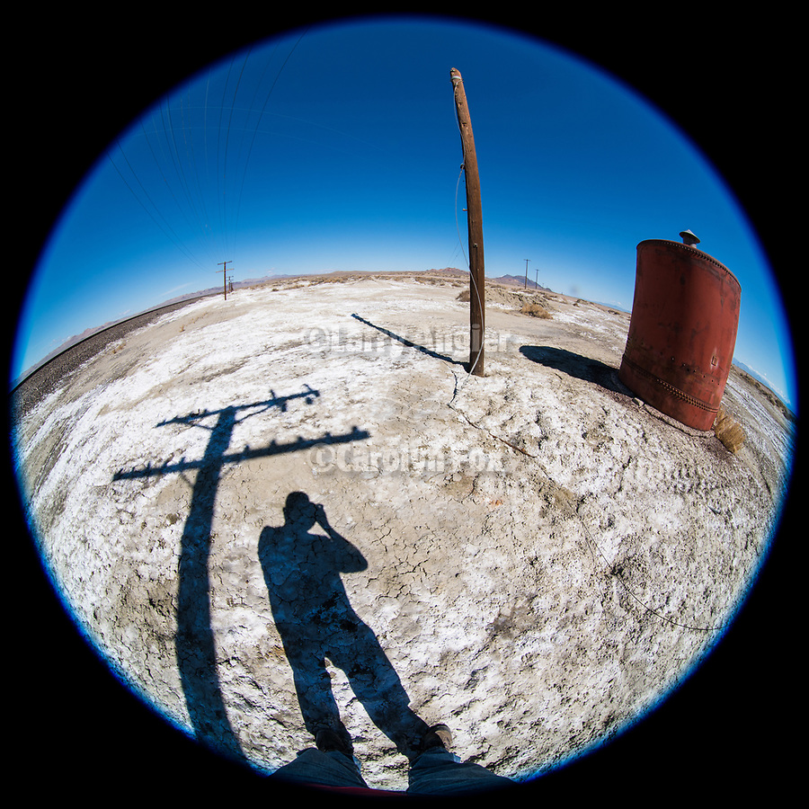 Telephone pole shadow with photographer, metal tank converted into a shed along the railroad tracks, Fortymile Desert, Nevada
