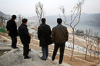 CHINA. Chongqing Province.  Men looking out over the town of Wushan, which lies on the banks of the Yangtze and at the entrance to the 3 Gorges. As tourism booms, towns are being developed and modernized resulting in old areas being razed.  The flooding of the three Gorges, by damming the Yangtze near the town of YiChang, has remained a controversial subject due to the negative environmental consequences and the displacement of millions of people in the flood plain. The Yangtze River however is reported to be at its lowest level in 150 years as a result of a country-wide drought. It is China's longest river and the third longest in the world. Originating in Tibet, the river flows for 3,964 miles (6,380km) through central China into the East China Sea at Shanghai.  2008.