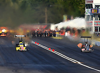 Aug. 1, 2014; Kent, WA, USA; NHRA top fuel dragster driver Antron Brown (left) races alongside Bob Vandergriff Jr during qualifying for the Northwest Nationals at Pacific Raceways. Mandatory Credit: Mark J. Rebilas-