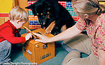Occupational therapist working with boy using therapy dog to encourage child in activity