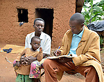 Emanuel Bizimungu  a community health worker in Rwanda, examines  a girl, Sandrine Uwase, two and a half, who he treated for malaria.  She is recovering.  They are  in Nyagakande village, near the Ruhunda health center in eastern Rwanda.
