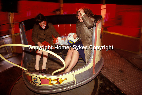 Two 1980s teenage girls on a Waltzer spinning around at the annual Kings Lynn mart Norfolk England. UK 1982