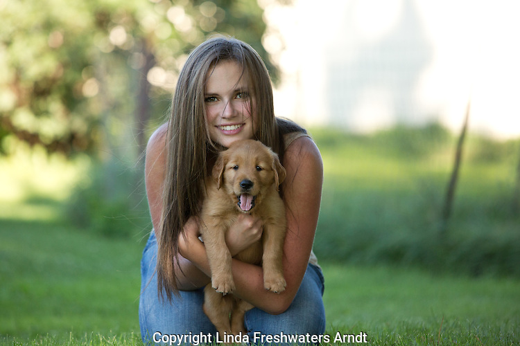 Young woman holding a golden retriever puppy