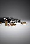 Handgun and bullets on white seamless