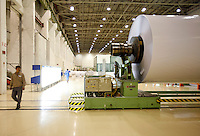 A worker walks by a large roll of paper at UPM Changshu Paper Plant in Changshu, China. At the price tag of 1 billion USD (830 million Euros), he UPM plant is the largest single investment made by a Finnish company in China..18 May 2006