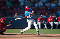 Spokane Indians third baseman Diosbel Arias (21) swings at a pitch in front of catcher Yorman Rodriguez (13) during a Northwest League game against the Vancouver Canadians at Avista Stadium on September 2, 2018 in Spokane, Washington. The Spokane Indians defeated the Vancouver Canadians by a score of 3-1. (Zachary Lucy/Four Seam Images)