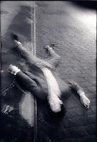 Man'sbody laying on cobblestone street<br />