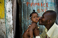 Haitian community leader kisses a baby girl in the slum of Cité Soleil, Port-au-Prince, Haiti, 24 July 2008. Cité Soleil is considered one of the worst slums in the Americas, most of its 300.000 residents live in extreme poverty. Children and single mothers predominate in the population. Social and living conditions in the slum are a human tragedy. There is no running water, no sewers and no electricity. Public services virtually do not exist - there are no stores, no hospitals or schools, no urban infrastructure. In spite of this fact, a rent must be payed even in all shacks made from rusty metal sheets. Infectious diseases are widely spread as garbage disposal does not exist in Cité Soleil. Violence is common, armed gangs operate throughout the slum.