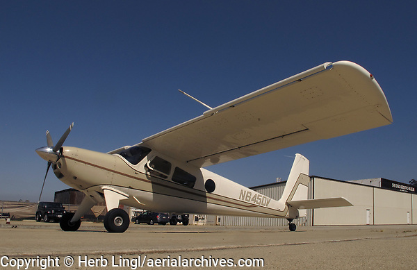 Helio Courier, N6450V, a H-295 model at Gillespie Field (SEE), El Cajon, San Diego County, California; one of the hangars of the San Diego Aerospace Museum is visible in the backgroubd