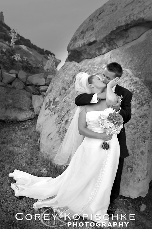 Bride and groom steal away for a kiss behind a rock.