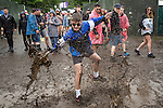 © Joel Goodman - 07973 332324 . 11/06/2016 . Manchester , UK . A reveller splashes through a muddy puddle at the Parklife music festival at Heaton Park in Manchester . Photo credit : Joel Goodman