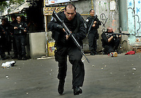 A policeman runs during operation at Vila Cruzeiro slum, Rio de Janeiro, Brazil, November 25, 2010. Authorities in Rio de Janeiro try to control a fourth day of violence apparently orchestrated by drug gang members who have attacked police stations and burned cars in Rio de Janeiro city as protest by traffickers after being forced from their turf by police occupations of more than a dozen slums in the past two years..(Austral Foto/Renzo Gostoli)