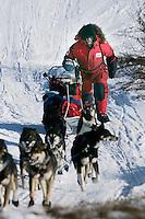 Sunday March 11, 2007   ----   Lance Mackey runs up a hill nearing Unalakleet on Sunday afternoon.