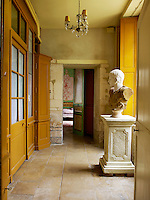 A 19th century bust is displayed in a stone-flagged corridor leading to one of the salons
