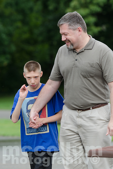"Michael McCollum<br /> 8/2/18<br /> David Overman arrives with his son Ryan,13,at the reveal ceremony where it was announced to Ryan Overman of west Knoxville that The Wish Connection is granting Ryan's wish to go to Washington DC and visit the White House at Carl Cowan Park, 10058 S Northshore Dr, Knoxville, TN , Thursday, August 2, 2018 at 5:45pm. Approximately 50-60 people attended, including the Overman family, friends, and AT&T Employees. The Bearden High School Cadets also attended and lead the pledge of allegiance.<br />  The AT&T Wish Connection is going to send Ryan, his family, and his service dog to Washington DC and while they are gone, the group of volunteers will be doing a makeover on his bedroom and turn it into the ""Oval Office"" at the White House.<br /> Ryan was born two weeks prematurely on May 13, 2005.  During the pregnancy he was classified as high risk due to a measured lack of growth and, after a brief stay in the hospital, he came home weighing only 4 lbs 5 oz.  His development was much slower compared to his peers, such as not learning to walk until he was well over a year old, and he was much smaller. The Overman family worked with Tennessee Early Intervention Services (TEIS) when Ryan was about one year old and with their help they were able to get Ryan enrolled through TEIS to receive Occupational, Physical, and Speech Therapy.  When Ryan turned three he transitioned from TEIS to the Knox County Early Intervention Program and began attending a special school to continue his therapies until he was old enough to enroll at Cedar Bluff Elementary and now is at Cedar Bluff Middle School. In 2016, Ryan was diagnosed to have retinitis pigmentosa, a degenerative disease of the retinas that under the best of circumstances causes severe tunnel vision, but more commonly results in complete blindness.<br />  Despite the physical difficulties that Ryan has had to endure over the last thirteen years, he continually brightens the lives of those around him.  If someone is h"