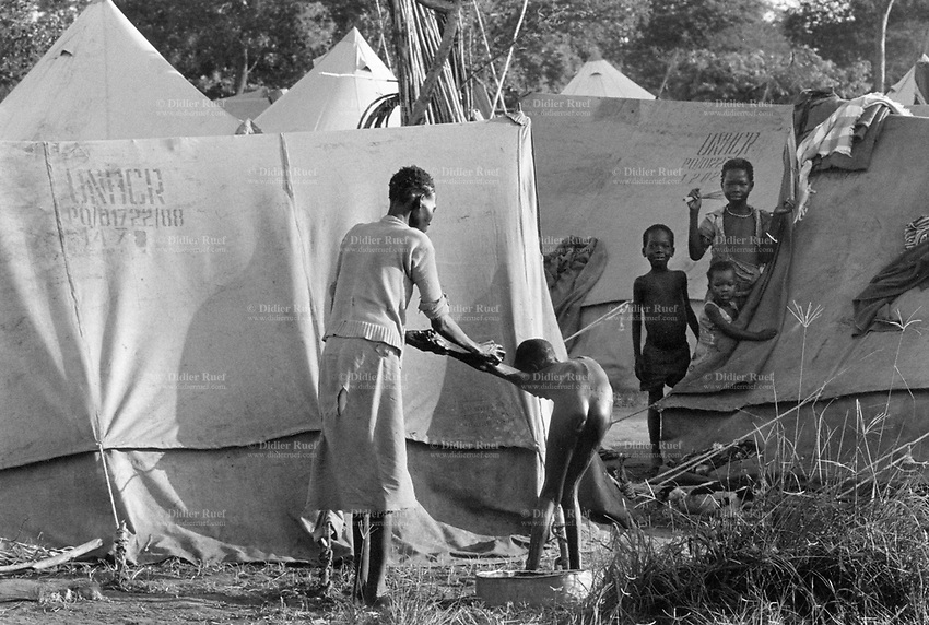 Uganda. West Nile. Adjumani. Ogujebe is distant 15 km from Adjumani. It is a transit camp for refugees from South Sudan. People stand by UNHCR tents. A mother is giving a bath and cleaning her child . West Nile sub-region (previously known as West Nile Province and West Nile District) is a region in north-western Uganda. © 1989 Didier Ruef
