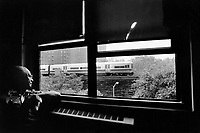 """USA. New York City. Spanish Harlem. Alejandro, a senior citizen and an immigrant from Puerto Rico, is looking outside of his flat's window on the MTA daily rail service to Connecticut. The Puerto Rican man and his family lives below the poverty line and receives public assistance (AFDC, Home Relief, Supplemental Security Income and Medicaid). The family resides in units managed by the New York City Housing Authority (NYCHA) which provides housing for low income residents. NYCHA administers rental apartments in facilities, popularly known as """"projects"""". Spanish Harlem, also known as El Barrio and East Harlem, is a low income neighborhood in Harlem area. Spanish Harlem is one of the largest predominantly Latino communities in New York City. 28.06.88 © 1988 Didier Ruef ."""
