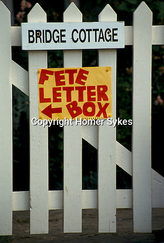 'ENGLISH VILLAGE FETE', THE VILLAGE FETE SIGN ON THE GATE OF A COTTAGE.