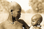 A Dinka woman in Kotobi, South Sudan holds her child in her arms.