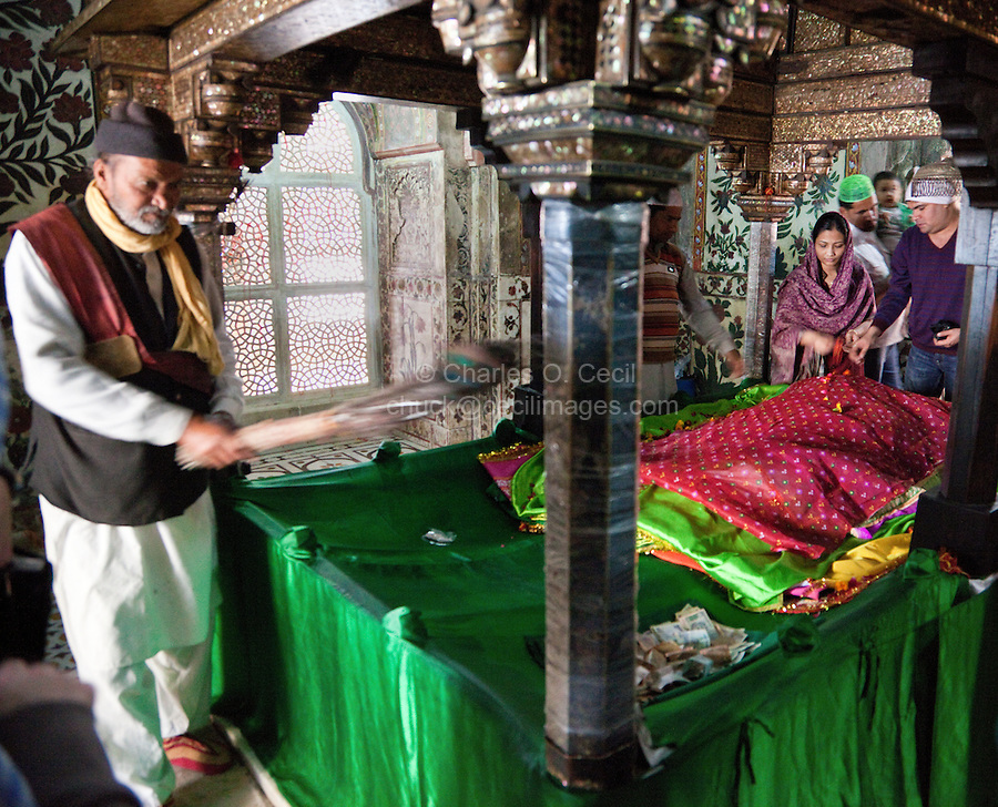 Fatehpur Sikri, Uttar Pradesh, India.   A Couple Visiting the Mausoleum of Sheikh Salim Chishti.  Prayers are often offered in hopes of conceiving a child.  Woman tosses rose petals on the tomb.