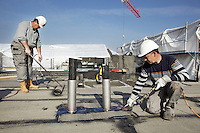 Switzerland. Geneva. Two roofer workers from the company Cerutti Toitures SA are installing roofing felt with heat using torches and flame (gas blowpipe torch) to waterproof the roof surface. 27.03.14  © 2014 Didier Ruef