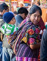 Chichicastenango, Guatemala.  Quiche (Kiche, K'iche') Woman in the Market Carrying her Son on her Back.