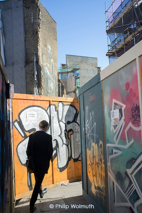 Murals on hoardings around a demolition site in Hoxton, London.  The area is undergoing intensive redevelopment, with new residential and office blocks squeezing out Silicon Roundabout tech start-ups and other small businesses.