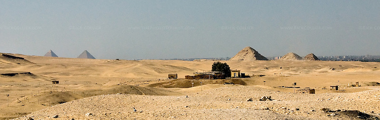 Saqqara, Cairo, Egypt -- There are hundreds of pyramids in Egypt.  Many are easily visible all around the famous step pyramid of Djoser (Dozer).  (The impressive and famous pyramids at Giza are visible on the left of this panorama, with Cairo in the distant background.) © Rick Collier / RickCollier.com