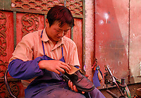 A young cobbler works under a shady red awning in alley off the Barkhor, Lhasa, Tibet.