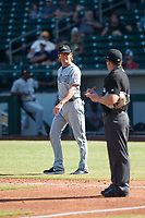 Peoria Javelinas pitching coach Pete Zamora (44), of the San Diego Padres organization, laughs with home plate umpire Bryan Fields on his way to the pitcher's mound during an Arizona Fall League game against the Mesa Solar Sox at Sloan Park on October 24, 2018 in Mesa, Arizona. Mesa defeated Peoria 4-3. (Zachary Lucy/Four Seam Images)