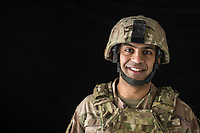 Close up studio portrait of  American Army soldier Ali looking at camera with black background
