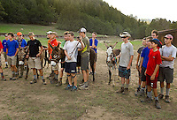 Photo story of Philmont Scout Ranch in Cimarron, New Mexico, taken during a Boy Scout Troop backpack trip in the summer of 2013. Photo is part of a comprehensive picture package which shows in-depth photography of a BSA Ventures crew on a trek.  In this photo BSA Venture Crew Scouts  prepare to race their burros down a hillside during the nightly team burro racing at Harlan Camp  in the backcountry at Philmont Scout Ranch.   <br /> <br /> The  Photo by travel photograph: PatrickschneiderPhoto.com