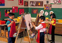 THREE SECOND GRADE STUDENTS WORKING ON THEIR PAINTINGS IN THE ART CLASS. SECOND GRADE STUDENTS. OAKLAND CALIFORNIA.