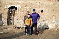 Grandmother Wang Bao Ying (left) and grandfather Fan Qing Huai stand with their orphan grandson Fan Lu Yang, 10, outside their home in Fanzhuang Village, Gangyun County, Jiangsu, China. The grandparents are both over 75 and often ill, and the income from growing corn, wheat, and hay, cannot support the three.  Fan Lu Yang's father died in 2000 in an accident at a small coal mine and his mother developed dementia and disappeared about a year before this picture was taken...At the time of the picture, China's Amity Foundation charity, was investigating the family's situation in preparation to raise money to financially support these children and other orphans in similar situations.  With Amity's support, each orphan, aged 6-12, would receive approximately 1,400 RMB annually (about 200 USD) to pay for the cost of living. Amity works to keep children out of the institutional orphanages in China, preferring to provide monetary assistance that can help maintain a family environment for the orphans it helps.
