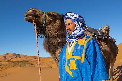 Morocco, Meknes-Tafilalet, Merzouga: Erg Chebbi, large dunes formed by wind-blown sand, with Moroccan man in traditional dress and camel   Marokko, Meknes-Tafilalet, Merzouga: Erg Chebbi, durch Verwehungen entstandene Duenen, und Einheimischer in traditioneller Kleidung mit Kamel