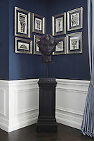 Architectural prints of classical ornamentation hang on the walls behind a Grecian head in a corner of the reception room