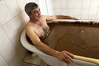 Azerbaijan. Naftalan region. Naftalan. Health center. A man lies in a bathtub filled with petrol. An ancient treatment to cure various ailments, such as arthritis and soreness. © 2007 Didier Ruef