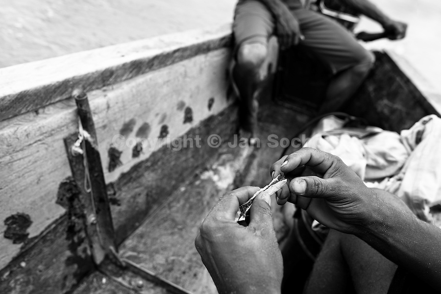 A Colombian sand miner rolls up a marijuana joint while crossing the river Magdalena in Puerto Berrío, Colombia, 3 February 2013. Artisanal (unmechanised) sand mining is an ancient mining technique used to obtain sand for construction purposes. Depending on the natural conditions (strength of the stream, depth of the river etc.), together with the sand miners' physical condition, the material is extracted in metal buckets, either by standing on the river bottom and searching for sand by feet, or, diving up to 3-5 meters deep using a wooden plank with steps. In spite of the physically demanding work, a sand miner's daily salary does not exceed 15-20 US dollars. However, the sand miners are very proud of their profession, valuing their work freedom above all, and usually, as long as their health and strength permit, they keep facing the river stream.