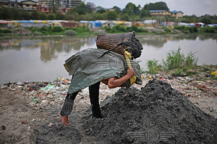 A woman collects sand from a dirty river that she will sell for10 rupees per basket.