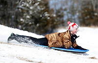 Jake Omohundro (cq), 10, signals to his mom Thursday, February 18, 2021, as he sleds down a hill at Kessler Mountain Regional Park in Fayetteville. The National Weather Service forecast for Friday is mostly sunny skies with a high near 37 degrees. Check out nwaonline.com/210219Daily/ and nwadg.com/photos for a photo gallery.<br /> (NWA Democrat-Gazette/David Gottschalk)