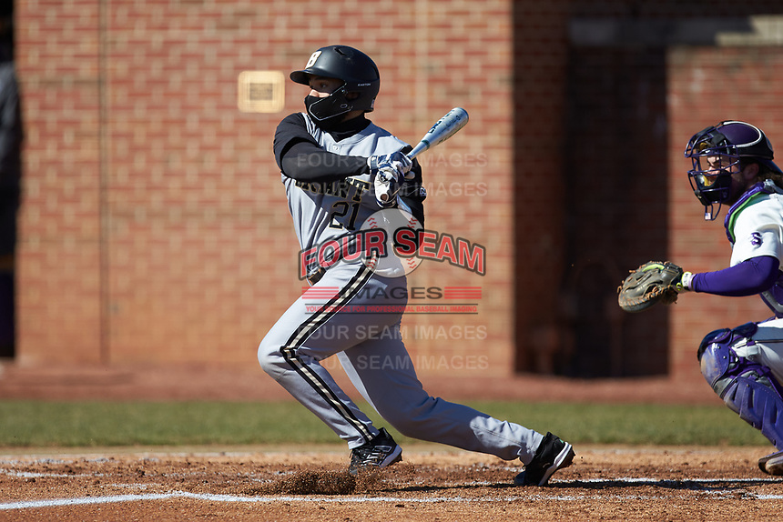 Brian Nicolas (21) of the Bryant Bulldogs follows through on his swing against the High Point Panthers at Williard Stadium on February 21, 2021 in  Winston-Salem, North Carolina. The Panthers defeated the Bulldogs 3-2. (Brian Westerholt/Four Seam Images)